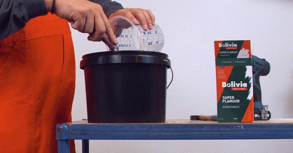 Bolivia plamuren op poederbasis: Geopend pak 'Super Plamuur' staat op werktafel, met emmer ernaast, waar water in wordt gegoten om plamuur aan te maken.